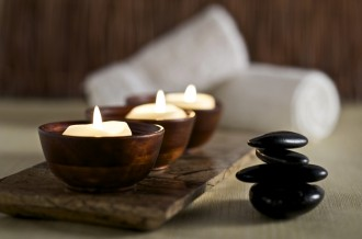 Lit candles and black massage stones in Zen spa